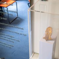 The exhibition Gijs Bakker & K. Schippers: Basics in Sonneveld House (11.07.2020 - 10.01.2021). The image shows Ronaldo, Gold under Titanium (377) by Gijs Bakker and the text of the poem Emballage by K. Schippers. Photo: Johannes Schwartz.